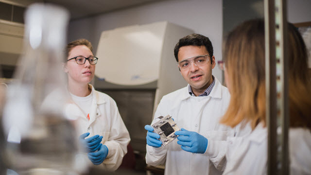 Sudeep Popat (center) holds a microbial fuel cell while working with students at Clemson University's L.G. Rich Environmental Research Laboratory