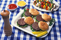 Hamburgers and fixings on a blue gingham tablecloth