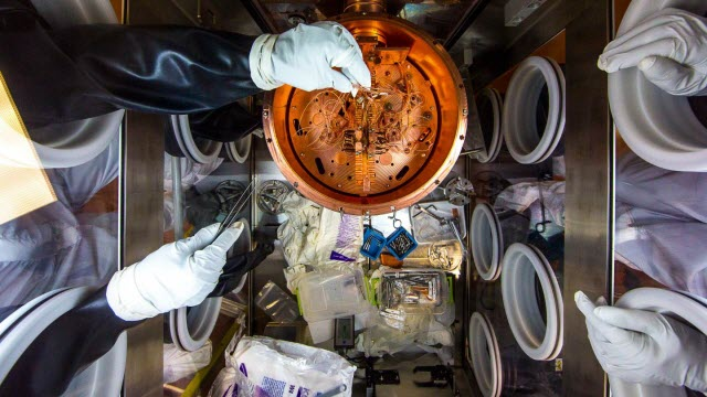 Researchers work on the delicate wiring of a cryostat