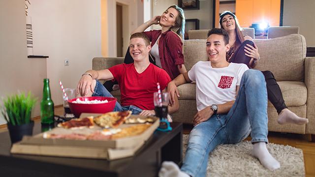 teens watching TV while eating junk food