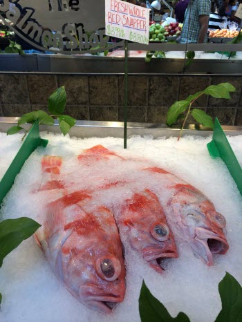 Fish labeled as red snapper are seen on ice in a fish market