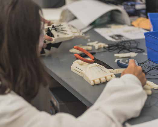 An upper-school student from the Awty International School works on a prosthetic hand that she 3D-printed during a Biomaterials Lab internship program.
