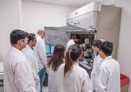 A postdoctoral researcher shows a group of attendees how to tissue-engineer scaffolds during the Biomaterials Lab's 2018 Biofabrication Workshop.
