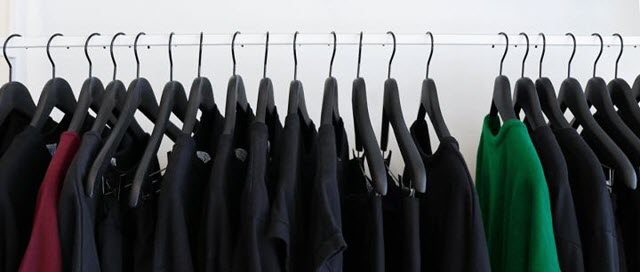 Heterogeneity in the workplace represented by similar-colored shirts on a clothes rack